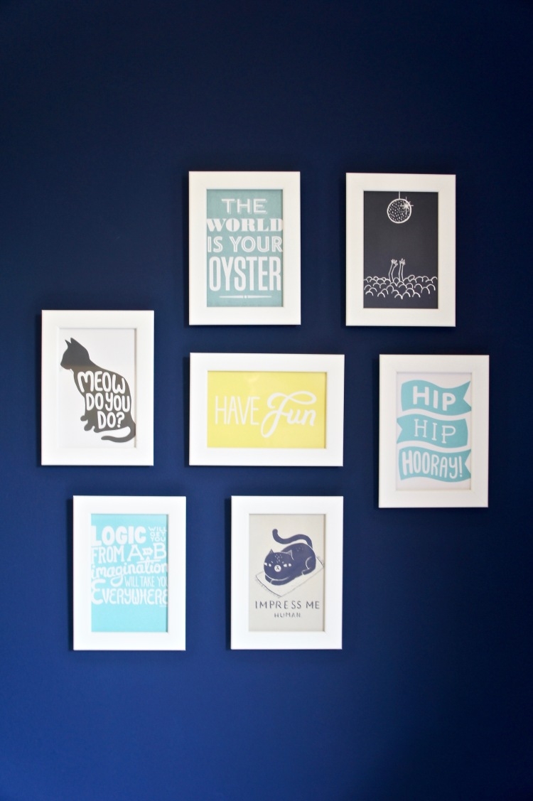 Navy blue wall with postcard gallery wall